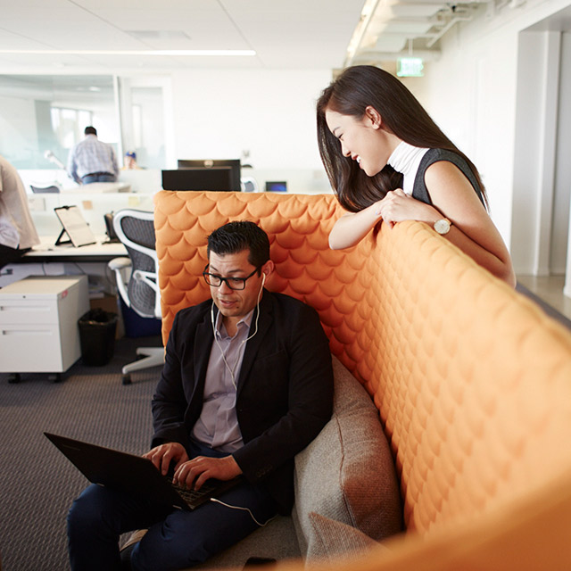 Man with a laptop sitting on a couch while a woman looks over him.
