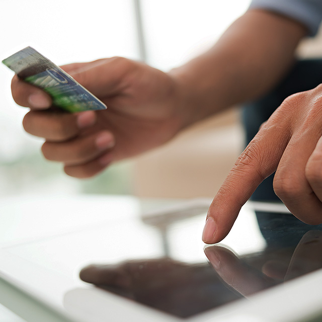Close up of man holding a mobile phone and credit card near a desktop