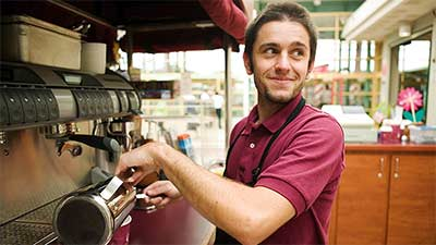 Barista turned to look at something off camera while smiling and making cup of coffee.