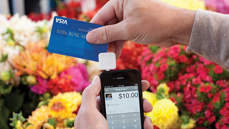 At a flower shop, a merchant swipes a Visa card through a Square reader attached to a phone.