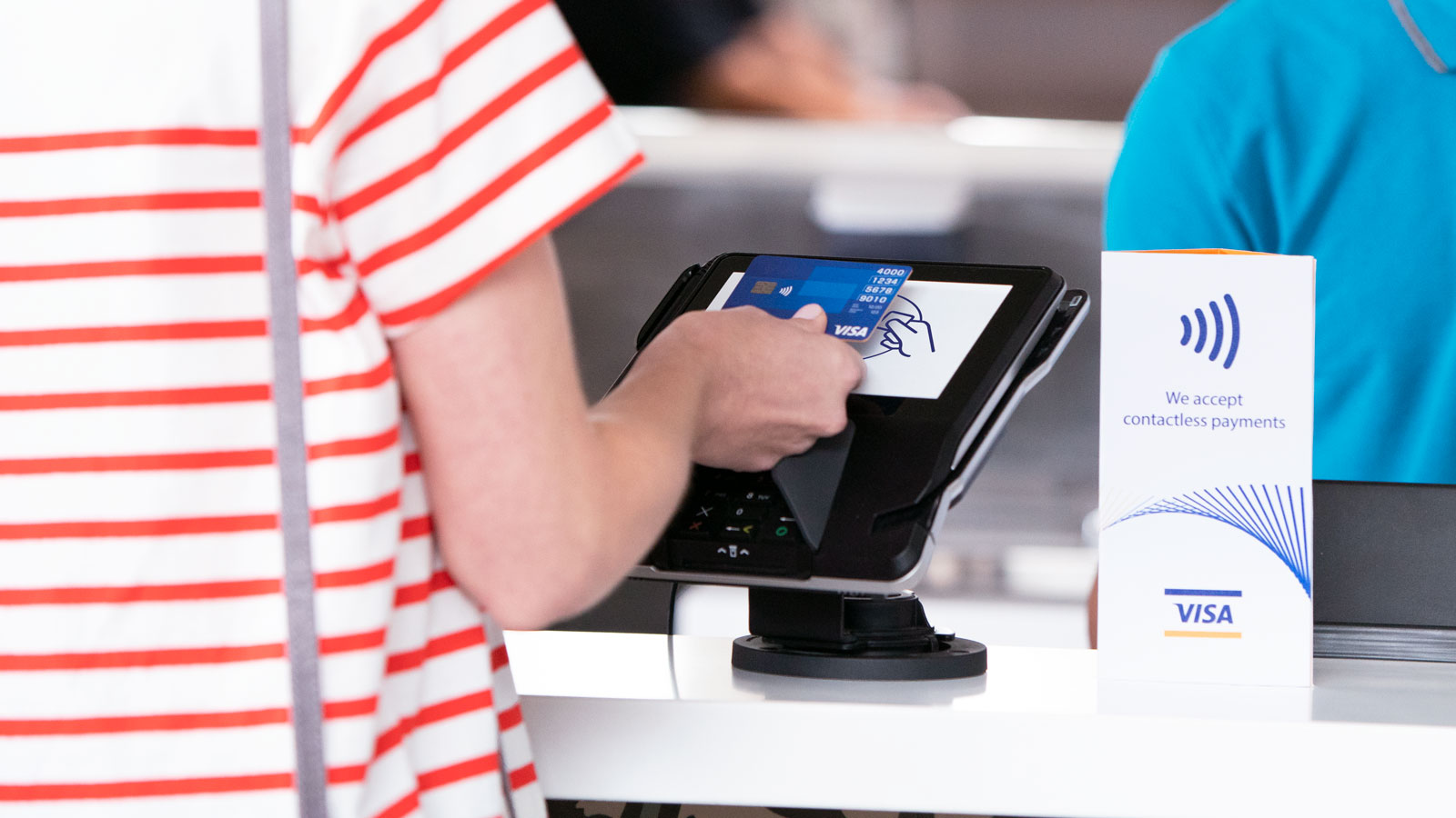 Woman paying with a Visa contactless card at a counter.